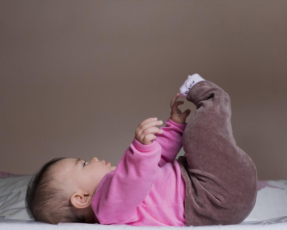 Baby op rug reikt naar benen